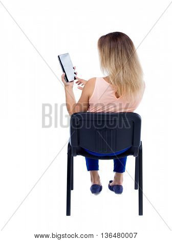 back view of woman sitting on chair and looks at the screen of the tablet.  Rear view people collection.  backside view of person.  Blonde in blue trousers sitting on the office chair and read e-books