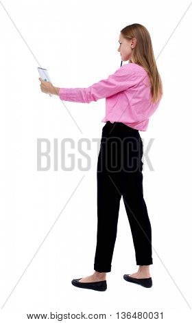 back view of  stands woman takes notes in a notebook.  Rear view people collection.  backside view of person.  Isolated over white background. Woman office worker in a pink shirt looks in a notebook