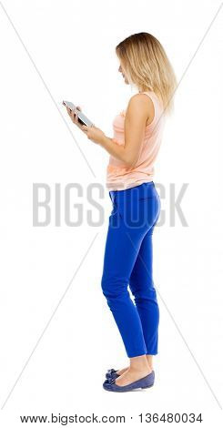 back view of standing young beautiful  girl with tablet computer in hands of. girl  watching. Isolated over white background. Blonde in blue pants and pink blouse stands sideways and looking at tablet