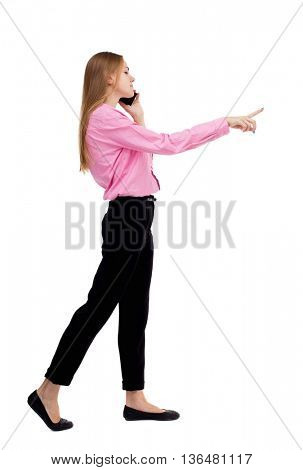 back view of walking  business woman . beautiful girl going, pointing and talking on smartphone.  Isolated over white background. Girl businessman checks the information on the tablet.
