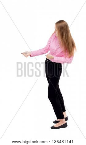 back view of standing business woman pulling a rope from the top or cling to something.  Isolated over white background. The girl office worker in black slacks standing sideways pulls on the rope.