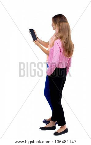 Back view of two young woman look at the smart phone. Rear view people collection.  backside view person. Isolated over white background. Two girls blonde stand cancer looking at tablet computer