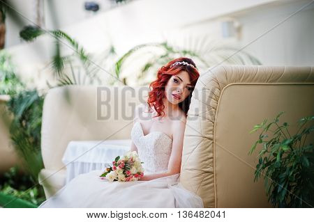 Portrait Of Charming Red-haired Bride Model With Wedding Bouquet At Hand Sitting On The Couch At The