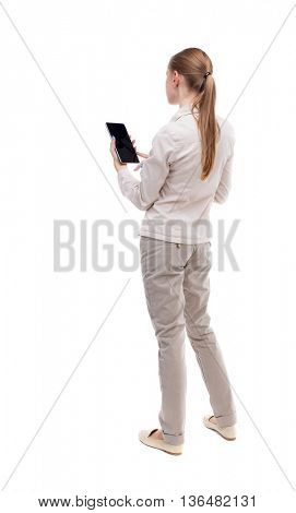 back view of standing young beautiful  girl with tablet computer in the hands of. girl  watching.   Isolated over white background. A girl in a white jacket looks in front of him holding a smartphone.