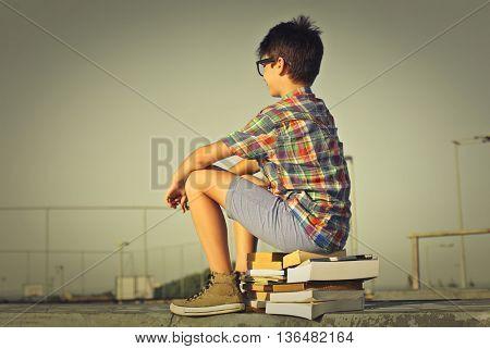 Teenager sitting on books