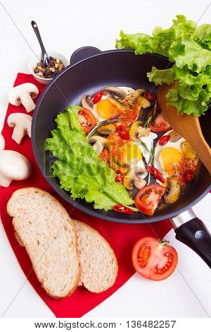 Homemade fried eggs in pan with tomato bread pepper and mushrooms on wooden background