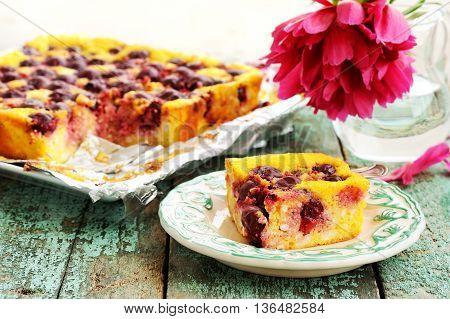 Homemade quark pie with chocolate sauce and red peony closeup