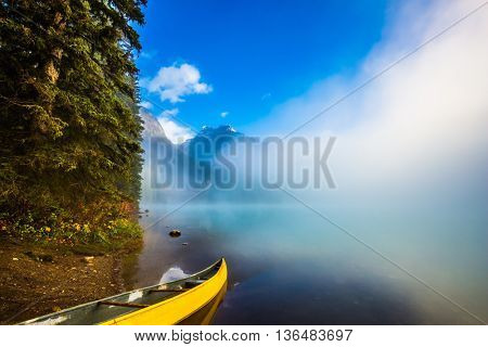 Foggy morning on Emerald Lake. Canada, Yoho National Park. Fishing boats moored on the shore
