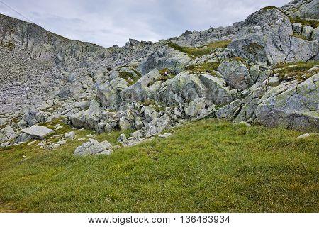 Rocks and green grass under Momin Dvor peak, Pirin mountain, Bulgaria