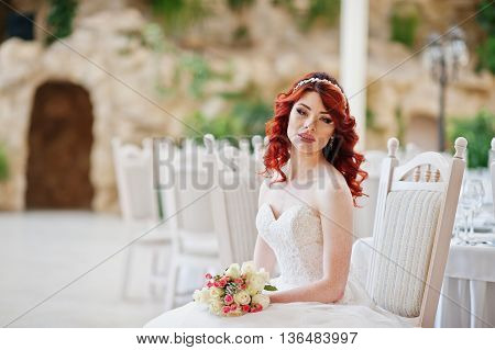 Portrait Of Charming Red-haired Bride Model With Wedding Bouquet At Hand Sitting On Chair At The Tab