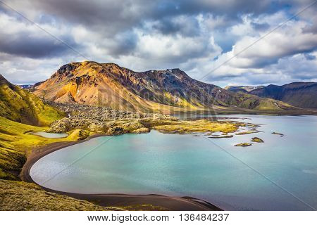 The magic of summer in Iceland. Cool blue water of the lake among the yellow-green tundra