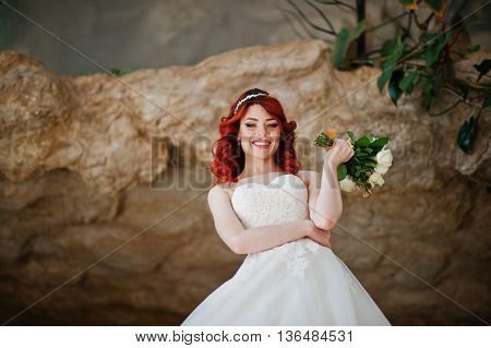 Charming Red-haired Bride Model With Wedding Bouquet At Hand Posed At Great Wedding Hall With Caves