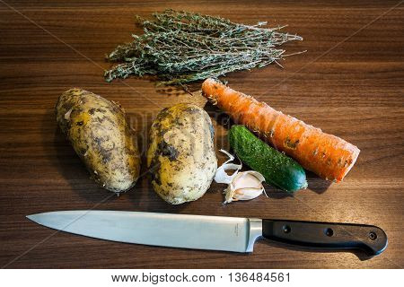 Potato tubers cucumber carrot garlic thyme and chef's knife on a wooden table.