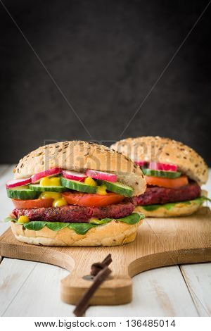 Veggie beet burger on white wooden table and slate background