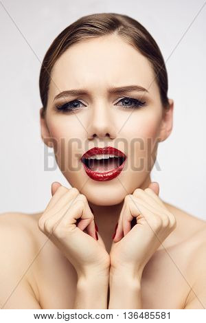 Fashion portrait of gorgeous young blond woman with red lips and nails. Shallow depth of field