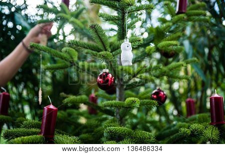 Decorating Christmas tree with ornament at home