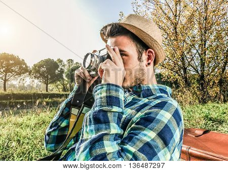 Young man with retro photo camera shooting wild nature - Handsome tourist traveling around the world during spring summer time - Fashion travel and lifestyle concept - Focus on left hand