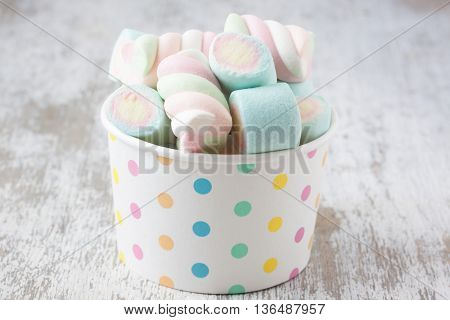 assorted marshmallow candies on a rustic wooden background