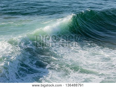 Sea surf wave with foam and splashes. View from beach.