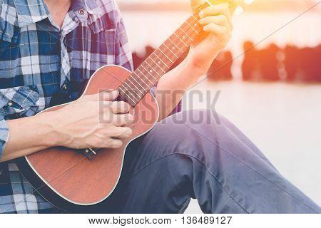 Handsome man play guitar (ukulele) in sunset evening background