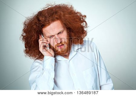Portrait of puzzled man with long red hair talking on the phone on a gray background