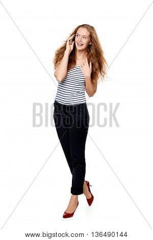 Full length portrait of young, happy beautiful woman talking on cell phone looking to the side at blank copy space, over white background