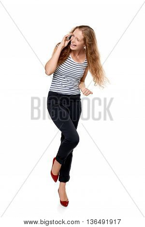 Full length portrait of young, happy laughing beautiful woman talking on cell phone showing yes gesture celebrating success, over white background