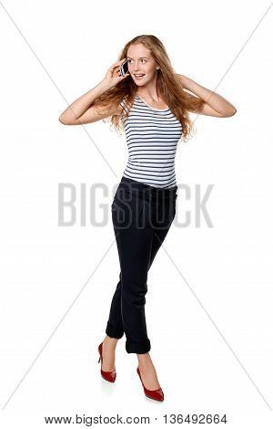 Full length portrait of young, happy beautiful woman talking on cell phone, over white background
