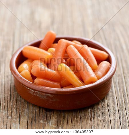 an earthenware bowl with some baby carrots on a rustic wooden surface