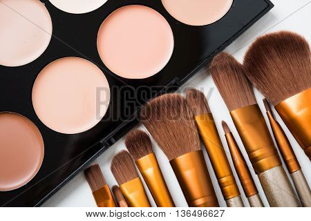 Professional makeup brushes and tools, natural make-up products set, eyeshadows and concealers on white table.