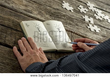 Businessman writing in a motivational book filled with analytical charts and burning lightbulbs for bright ideas on an old rustic wooden desk with scattered jigsaw puzzle pieces alongside.