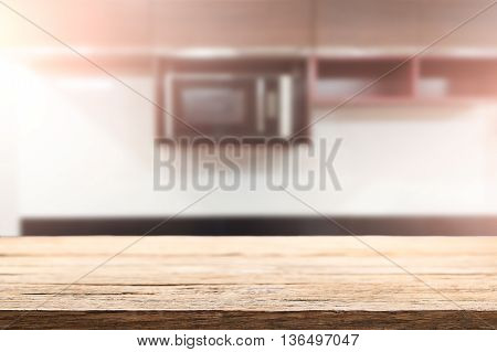 Empty wooden table space over blurred kitchen background for product display montage.