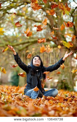 Autumn woman at the park throwing leaves in the air