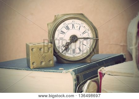Old clock with brass gambling cube with number six