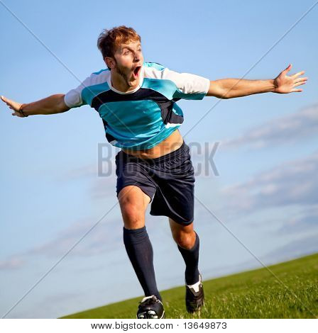 Footballer running on the field celebrating a goal