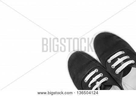 Black gumshoes with white laces isolated over white