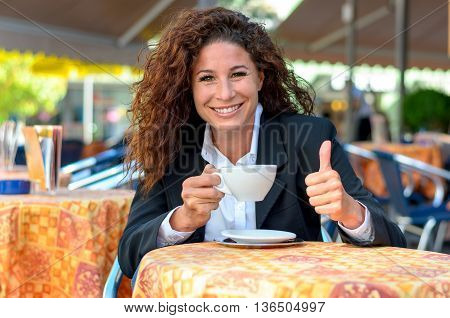 Happy young woman enjoying a cup of coffee at an open-air cafe looking at the camera with a beaming smile while giving a thumbs up of approval
