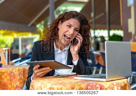 Frustrated attractive young businesswoman yelling into her mobile phone with her tablet and laptop in front of her as she sits at an outdoor restaurant