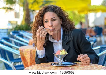 Attractive stylish young woman sitting at an open-air restaurant table savoring an ice cream sundae with different flavors of ice-cream