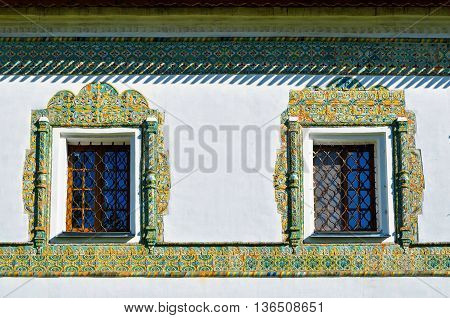 Windows framed with colorful ancient mosaic tiles. Nicholas Vyazhischsky stauropegic monasteryVeliky Novgorod Russia. Ornamental architecture architecture view closeup of architecture details