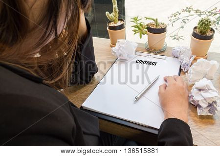 Stressed woman sitting at wooden desk with contract document and trash paper balls.