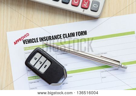 Top view of Approved vehicle insurance claim form with car key pen and calculator on wooden desk concept