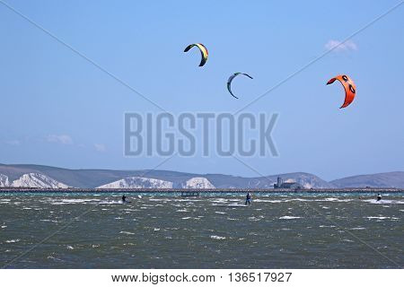 Kitesurfers riding in Portland Harbour in Dorset