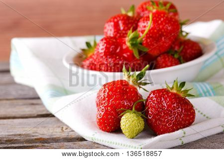 Red And Green Strawberries On Cloth In Front Of Bowl