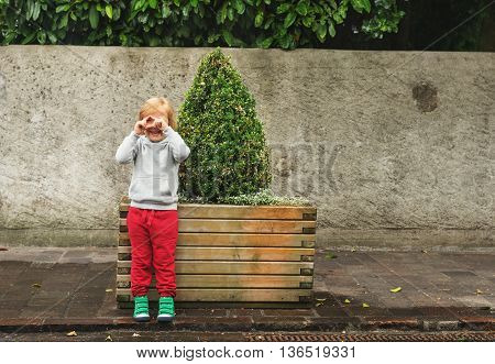 Fashion portrait of adorable toddler boy wearing grey sweatshirt, red trainings and green shoes. Kid pretending taking pictures with his hands