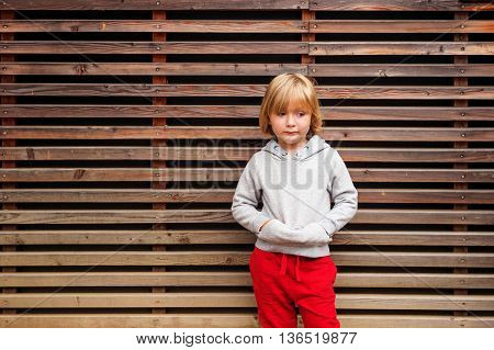 Fashion portrait of adorable toddler boy wearing grey sweatshirt and red trainings, standing against wooden background