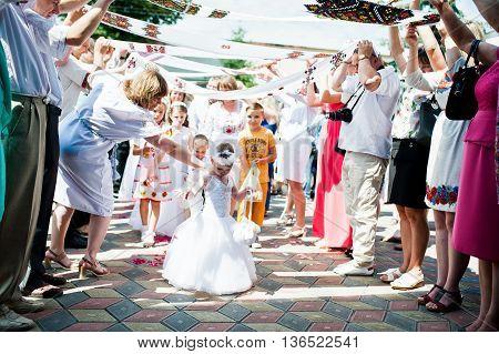 Mukyluntsi , Ukraine - 26 June, 2016: First Holy Communion. A Little Girl Dressed As An Angel Sprink
