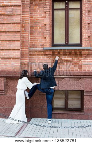 Bride is trying to climb on the windowsill of an old building and the bride is holding his