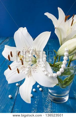 white lily flower on a blue background with beads, summer Still Life