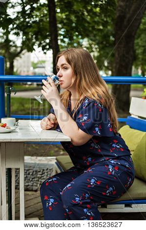 cute full girl on the summer terrace cafe sits on a sofa at a table holding a glass of white wine and drinks
